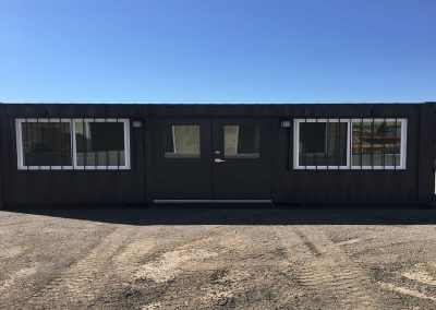 Job site office container with double doors and security bars on the windows.